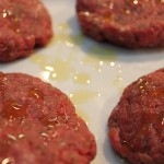 raw burgers drizzled with olive oil